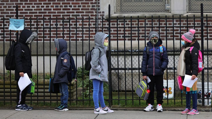 Children returning to school line up before entering P.S. 179 Kensington on December 07, 2020 in New York City. The New York City public school system opened for in-person learning 10 days after being shut down by Mayor Bill De Blasio due to a rising number of coronavirus (COVID-19) positive cases in the city.