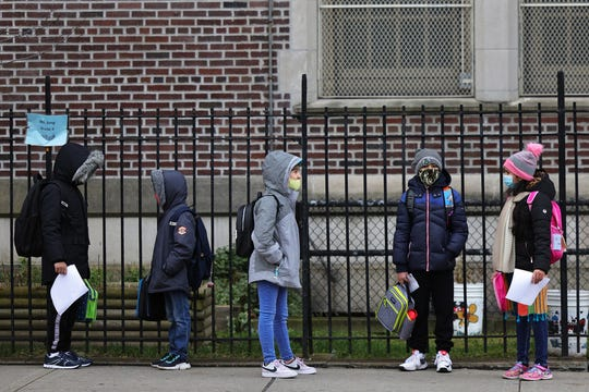 Children returning to school line up Monday before entering P.S. 179 Kensington in New York City. The New York City public school system has reopened for in-person learning after a pre-Thanksgiving shutdown due to rising COVID-19 cases in the city.