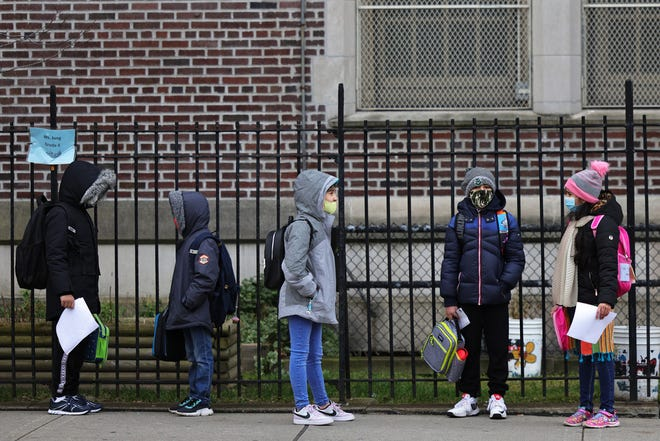 Children returning to school line up before entering P.S. 179 Kensington on December 7 in New York City. The city's public schools are open for some in-person learning, but the teachers' union is concerned about the rising rate of positive COVID-19 test results.