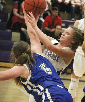 Wesleyan Christian School's Mackenzie Hendrix, right, fights valiantly for a 50-50 ball during girls varsity basketball action last season.