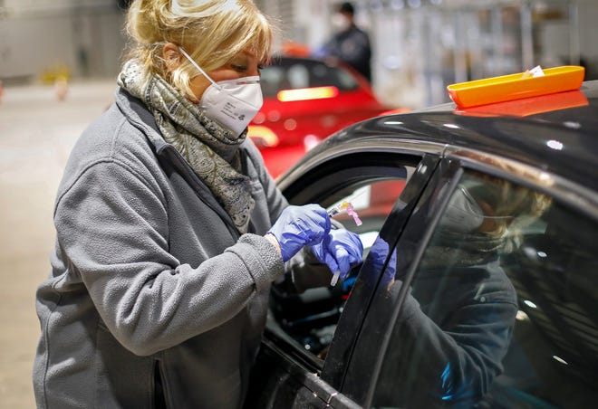 """Registered nurse Jane Dickson administers a flu shot in the drive-thru line at the Ohio State Fairgrounds in Columbus. With flu season off to mild start, experts say the feared """"twindemic"""" of flu and coronavirus outbreaks at high levels is less likely."""