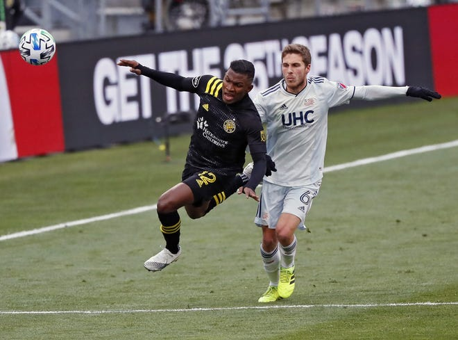 Crew winger Luis Diaz is fouled by New England midfielder Scott Caldwell during the first half of the MLS Eastern Conference final.