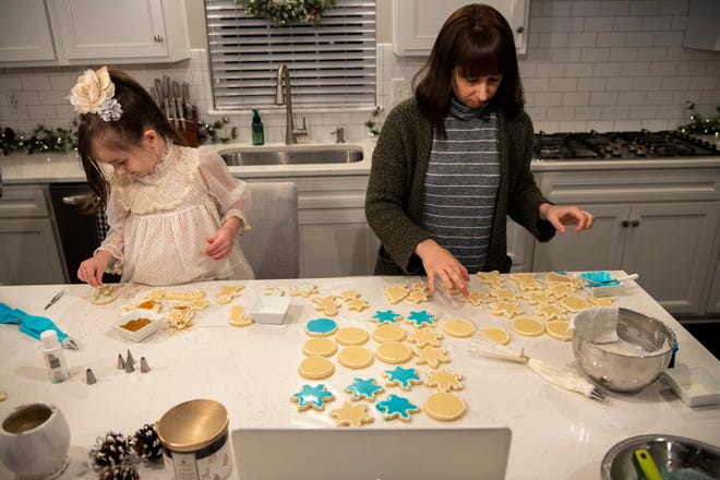 Isla Gillespie, 7, left, and her mother, Shannon Gillespie, work on putting icing and decorations on cookies during a Zoom call with extended family that took the place of their annual, in-person Christmas cookie decorating gathering.