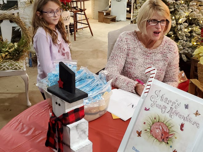 Local author Dianne Nicholas Goodrich thinks about what to write in her latest children's book for Sheets Memorial Christian School student Addyson McCullough. She held a book signing on Dec. 4 at Evenbrooke Marketplace, where her books may be purchased.