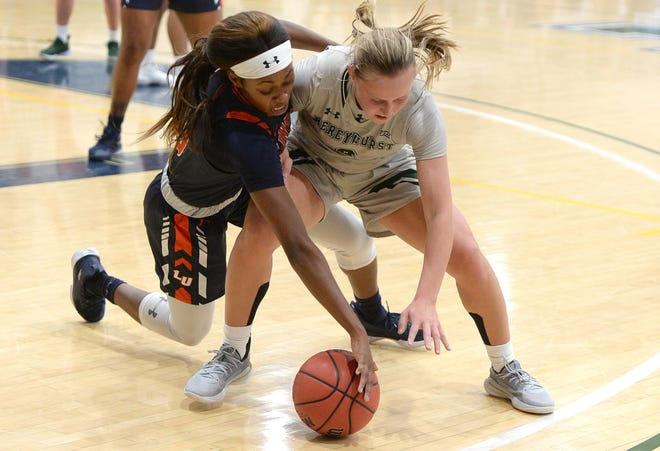 Mercyhurst's Emily Shopene battles for a loose ball with Lincoln's Bryanna Brown on Tuesday in the women's basketball game at the Mercyhurst Athletic Center in Erie.