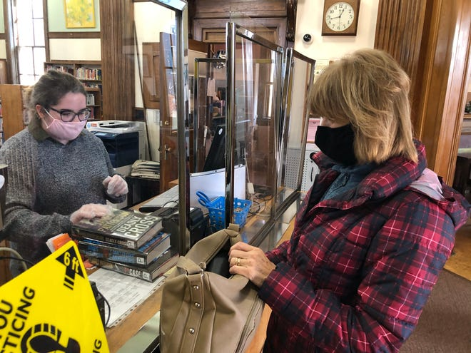 Hornell Public Library clerk Kristen Williams checks out books for patron Linda Markham as the library reopened Monday after closing for approximately nine months due to COVID-19.
