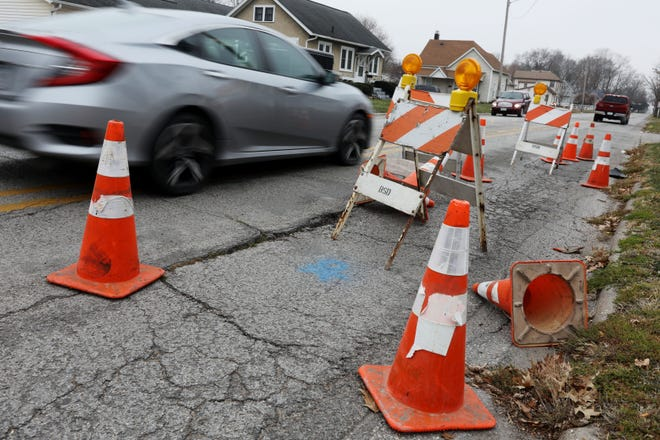 Traffic travels along Harrison Avenue next to a  sink hole Tuesday Dec. 8, 2020 near 12th Street in Burlington.