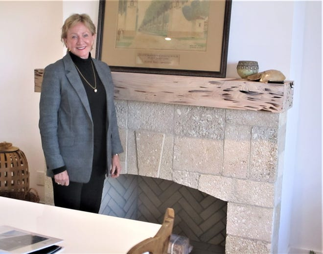 Peggy Cornelius stands near a fireplace with newly mined coquina rock from St. Augustine and a pecky cypress mantel. As the owner of Cornelius Construction Company in Neptune Beach, she is one of only two women in Duval County holding such a position.