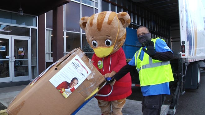 Daniel Tiger and and Franklin Cero, a Suddath delivery driver, deliver a box of sweaters as part of WJCT's Mister Rogers' Neighborhood Sweater Drive.