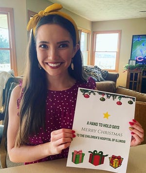 Sierra Brown, Cambridge, founder of A Hand to Hold ministry, holds the Christmas greeting she will take with her to the Children's Hospital in Peoria along with a check in the amount of money she has collected to benefit the children hospitalized over the holiday season.