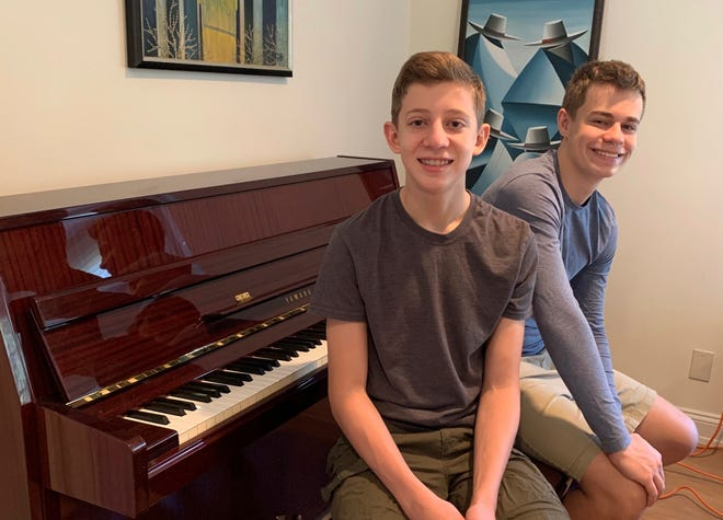 This Nov. 20, 2020 photo released by Andrea Fage shows brothers Rafael Fage, 16, background, and Noah Fage, 14, posing at the piano at their home in Harrison, N.Y. During the pandemic lockdown, private piano lessons for the boys stopped. They researched movie soundtracks and learned the score on their own with the assistance of sites like YouTube. (Andrea Fage via AP)