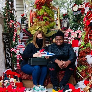 Lori Charlet poses with her neighbor, Trenton, who donated his Air Jordan shoes and volunteered to assist with the annual Santa Claus photo fundraiser.