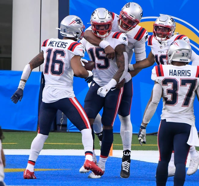 Patriots wide receiver N'Keal Harry (second left) gets a hug from quarterback Cam Newton (back middle) after catching a 5-yard touchdown pass in the third quarter against the Chargers at SoFi Stadium. Left is wide receiver Jakobi Meyers and wide receiver Damiere Byrd is at right. The Patriots are staying the week in Los Angeles as they get ready to play the Rams on Thursday night at SoFi Stadium. (Robert Hanashiro-USA TODAY Sports)