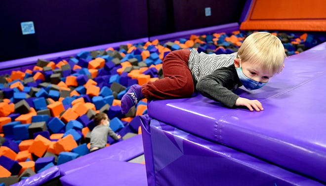 Cameron Weiner, 2,  of Wayland, climbs in the Trampoline Park at Apex Entertainment in Marlborough on Dec. 8. On Sunday, indoor recreational businesses will close as  part of Gov. Charlie Baker's rollback of the state's reopening plan.