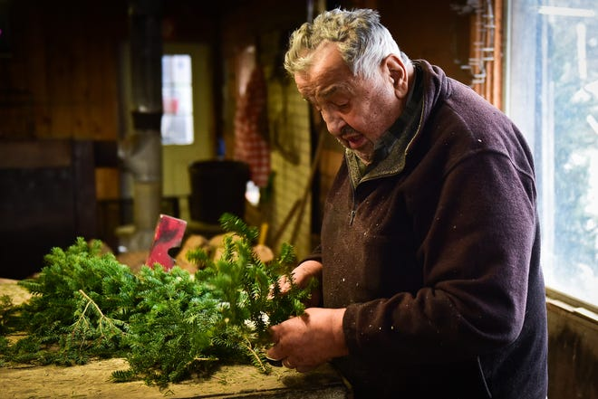 Omar Massoud, owner of Massoud's Tree Farm in Sauquoit, trims pine branches while making a wreath in his shop on Tuesday, Dec. 8, 2020.