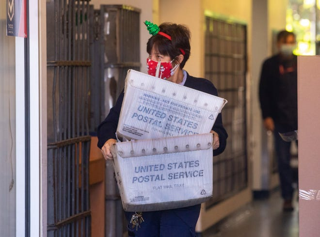 A postal worker carries boxes of mail as the post office at The Royal Poinciana Plaza reopens Tuesday after being closed since early October because of flooding issues. (DAMON HIGGINS/THE PALM BEACH DAILY NEWS)