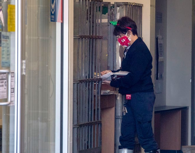 A postal worker sorts mail as the post office at The Royal Poinciana Plaza partially reopened Tuesday after being closed since early October.