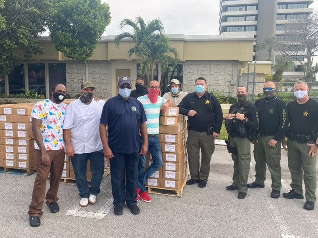 Volunteers from Living Hungry, which coordinates food-distribution  drives such as the one occurring Dec. 18, 2020 at Compson Place at Renaissance Commons in Boynton  Beach.
