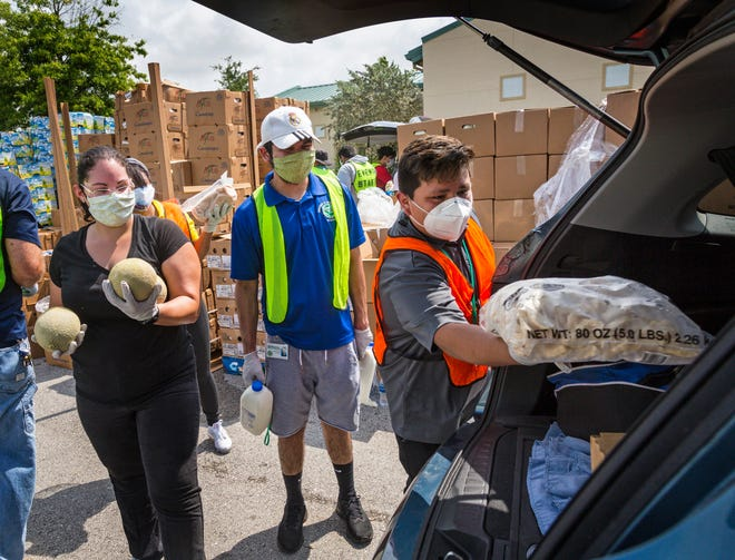 A mix of Greenacres city employees and volunteers load food from Feeding South Florida into vehicles at the Greenacres Community Center in April. At 9 a.m., when the distribution was scheduled to start, the line of cars waiting stretched 2-1/2 miles down 10th Avenue North, Jog Road, and onto Lake Worth Road. [LANNIS WATERS/palmbeachpost.com]