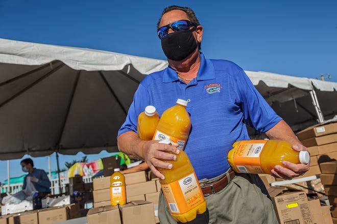 Jay Runtenberg, Wellington, helps distribute juices to motorists at the drive-through Feeding South Florida event at the Hatch 1121 building in Lake Worth Beach on Tuesday, Dec. 8.