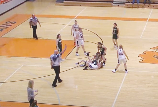 Pratt Lady Greenbacks go to the floor to pick up a loss ball in their opening game Friday against Larned.
