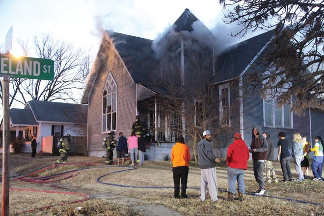 A crowd gathers at the corner of Cleveland and Pine streets last Tuesday when firefighters were called to put out a fire in a church that was home for several families and individuals in Pratt.