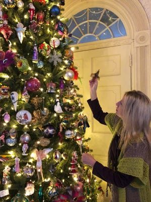 The Social Butterfly Kristi K. Higgins seeks a place to hang a butterfly ornament on designer Larry Davis' 12-foot Christmas tree at the Centre Hill Mansion Museum in Petersburg on Dec. 2, 2020.