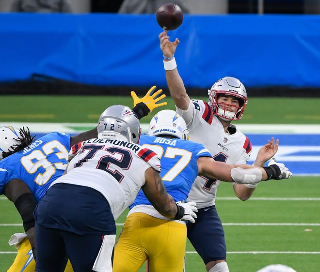 Patriots quarterback Jarrett Stidham gets off a pass while pressured by Chargers defensive end Joey Bosa (97) during the fourth quarter on Sunday at SoFi Stadium.