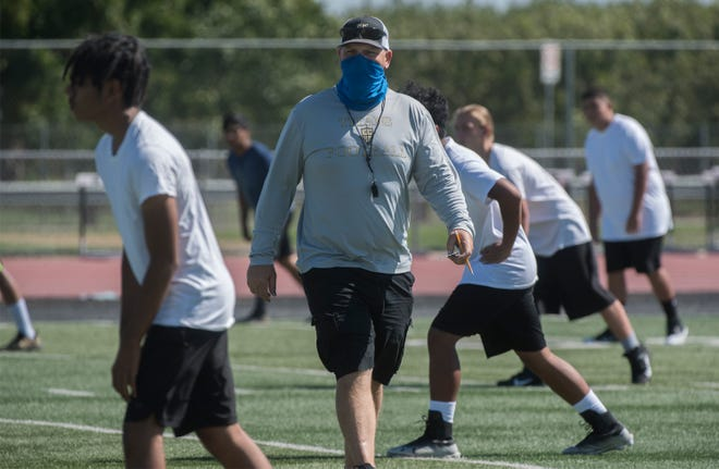 John Ward, head varsity football coach with Chavez High, runs player though a drill during a summer conditioning camp at the school in Stockton.
