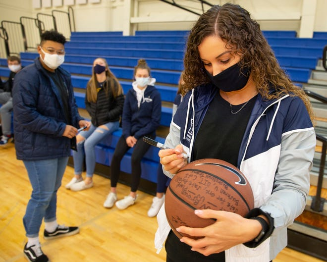 Earlier this month, Bushnell basketball player Sarah Reinecker, right, and other players from the men's and women's teams, signed a ball for Gov. Kate Brown asking her to allow their teams to play.