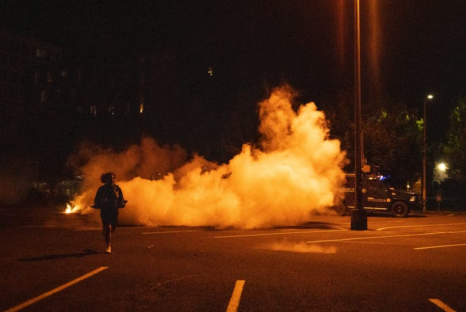 Eugene Weekly reporter Henry Houston runs out of the smoke of chemical munitions deployed by the Eugene Police during a demonstration near the University of Oregon in June.