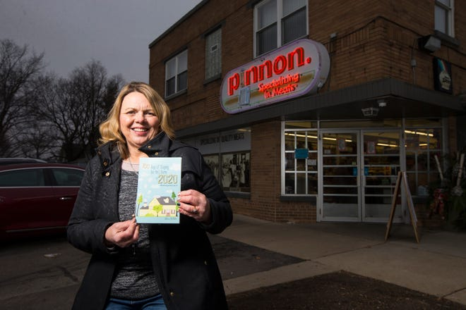 """Sheri White, author of """"100 Days of Staying the Hell Home in 2020 #HashtagsofCovid19,"""" poses in front of Pinnon's market, on Tuesday, Dec. 8, 2020, in Rockford. The market features prominently in her book."""