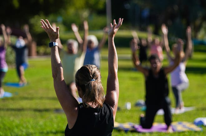 Yoga instructor Erin Hurter leads a free yoga class on the lawn at Van Wezel Performing Arts Hall on Saturday in Sarasota. About 60 people participated in the class.