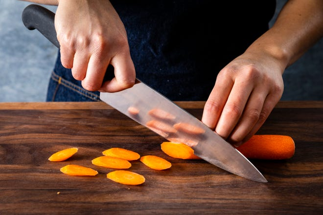 """GET A GRIP: The best chef's knife for you is the one that feels right. Hold the knife before you buy it. If possible, ask if you can use it to cut up something, like a carrot."""" (Photo courtesy of America's Test Kitchen)"""