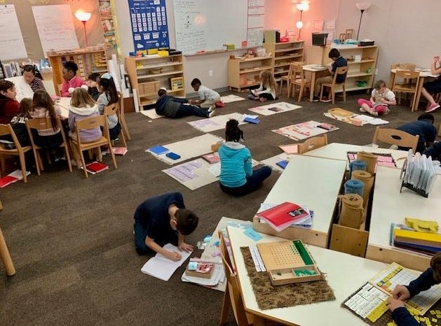 Students in a Lower Elementary classroom - mixed 1st through 3rd grades - is another fundamental of Montessori. The teacher is at the table giving a lesson and the other students are working.