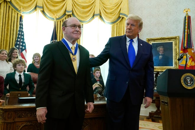 President Donald Trump congratulates Olympic gold medalist and former University of Iowa wrestling coach Dan Gable after awarding him the Presidential Medal of Freedom, the highest civilian honor, in the Oval Office of the White House, Monday, Dec. 7, 2020, in Washington.