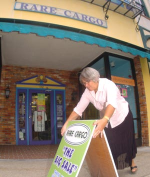 Mimi Kessler puts out a sandwich board in front of her downtown Wilmington business, Rare Cargo, in 2006. The gift and clothing shop closed later that year after 17 years downtown.