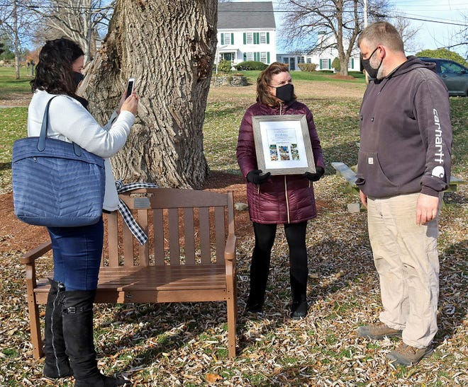 Meadowbrook Orchards owner David Chandler accepts a citation and bench from Operation: Food is Love program coordinator Jennifer Scalise-Mullett (center) as Rev. Robin Bartlett, of First Church in Sterling, captures the moment on her phone.