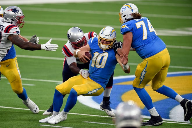 Los Angeles quarterback Justin Herbert is sacked by New England defensive tackle Adam Butler during the second half of Sunday's game.