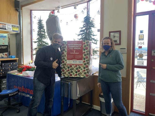 Sneakerama owner Steve Genatossio, left, and Central Mass Striders executive board member Kate Pietrovito promote Planting the Seed's community toy drive.