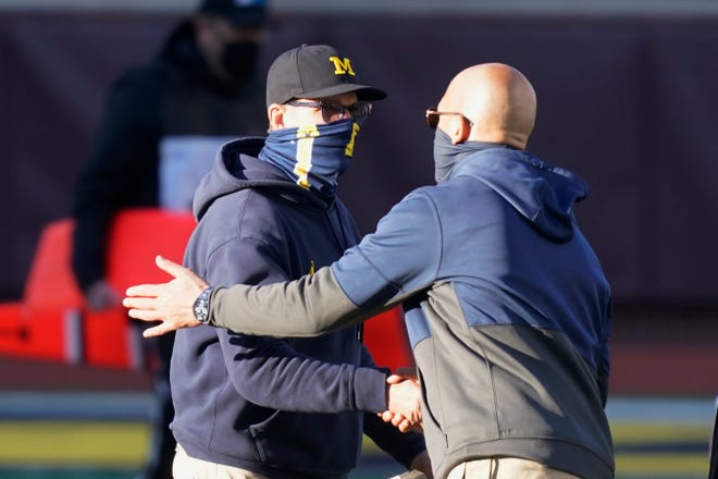 Michigan head coach Jim Harbaugh, left, greets Penn State head coach James Franklin after last month's game.