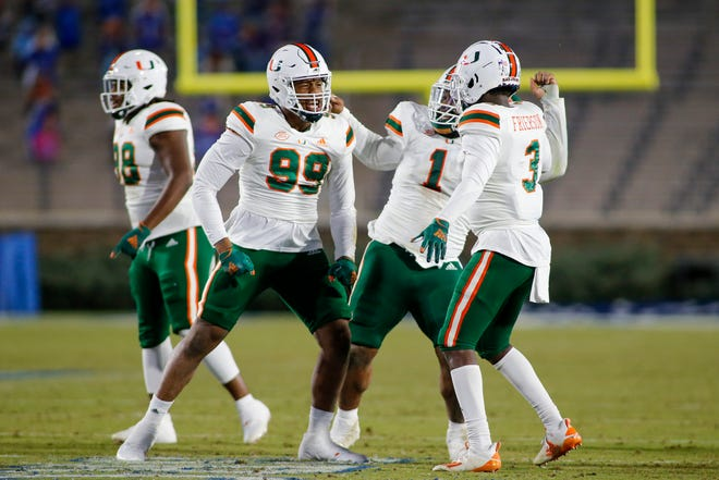 Miami Hurricanes defensive end Elijah Roberts (99) and defensive lineman Nesta Jade Silvera (1) and linebacker Gilbert Frierson (3) celebrate after a fumble recovery against the Duke Blue Devils in Durham last Saturday. Miami's defense will be tested by the high-powered offense of North Carolina this weekend.
