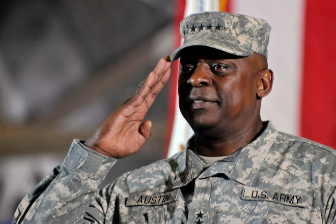 Then-Gen. Lloyd J. Austin III salutes during the playing of the national anthem after returning the United States Forces - Iraq colors to the U.S., Dec. 20, 2011, at Joint Base Andrews, Maryland. Austin was confirmed by the Senate as the nation's first Black secretary of defense Friday, Jan. 22, 2021.
