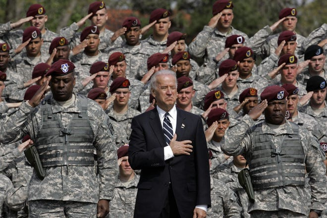 Vice President Joe Biden, center, is seen during the National Anthem during a welcome home ceremony at Fort Bragg on Wednesday, April 8, 2009. Biden welcomed home the 18th Airborne Corps from Iraq after their second deployment. At left is Lt. Gen. Lloyd J. Austin III, Commanding General XVIII Airborne Corps and Fort Bragg. At right is Command Sgt. Major Joseph Allen.