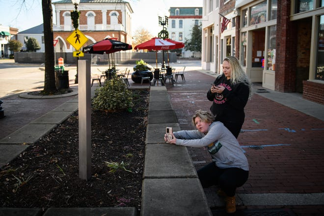 Paige Rossillo and Susie Monroe take photos of a mini monolith in a raised flowerbed Tuesday on Hay Street. The 3-foot-tall sculpture first appeared Dec. 3, and nobody as yet has taken credit for placing it there.