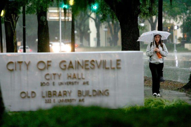 A woman walks under her umbrella past City Hall in downtown Gainesville.