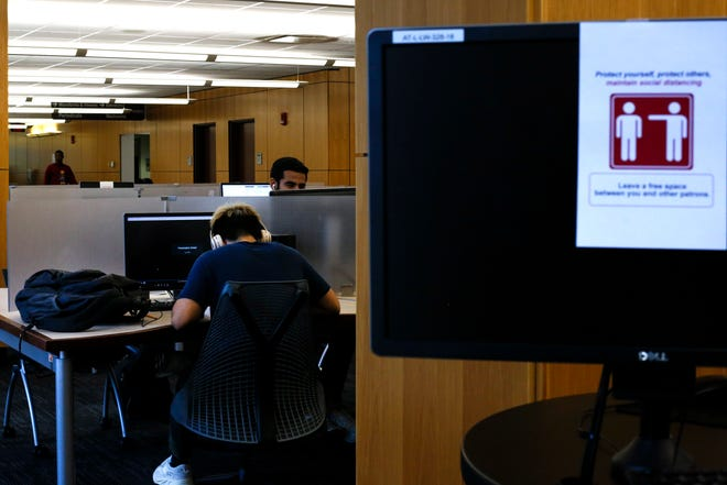 Students study and watch online lectures in Library West on the University of Floridaa campus in Gainesville. Signs placed around the library warn students to maintain social distancing.