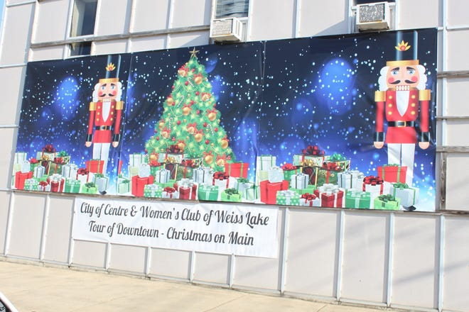 """A giant holiday banner showing Nutcracker ballet characters has been hung on the South River Street side of the Model Tees building in Centre. The colorful banner urges participation in """"Christmas on Main."""""""