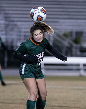 Mosley's Cailyn Lake puts her head on the ball in the first period. Arnold played Mosley in girls soccer Monday, December 7, 2020.