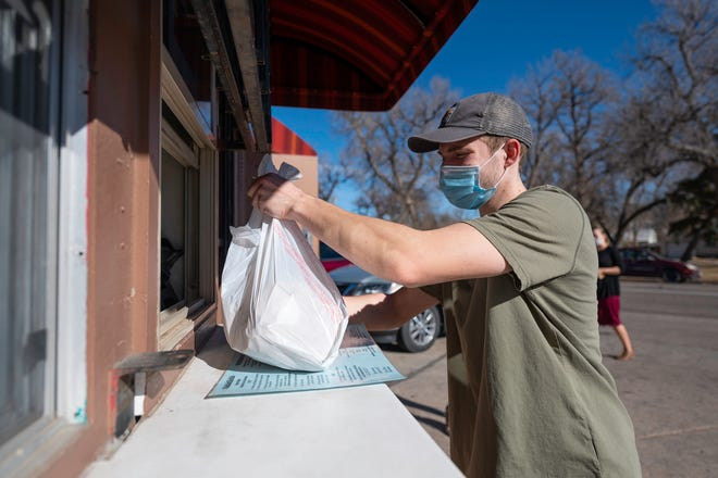 Alec Bond picks up a to-go order from Burrito's Betty on Tuesday. Under current COVID-19 restrictions, restaurants can offer carry out; delivery; and outdoor dining. (Chieftain Photo/Zach Allen)